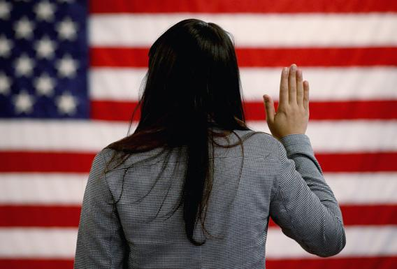 An woman takes the oath of allegiance during a naturalization ceremony at the at district office of the U.S. Citizenship and Immigration Services (USCIS) on January 28, 2013 in Newark, New Jersey.