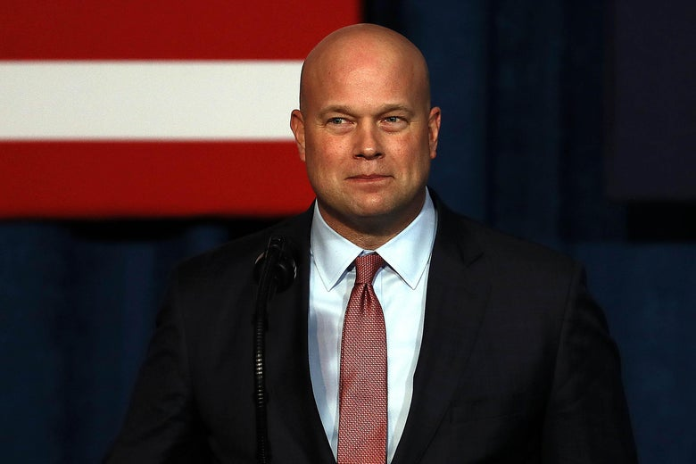 Whitaker squints slightly as he stands in front of a podium.