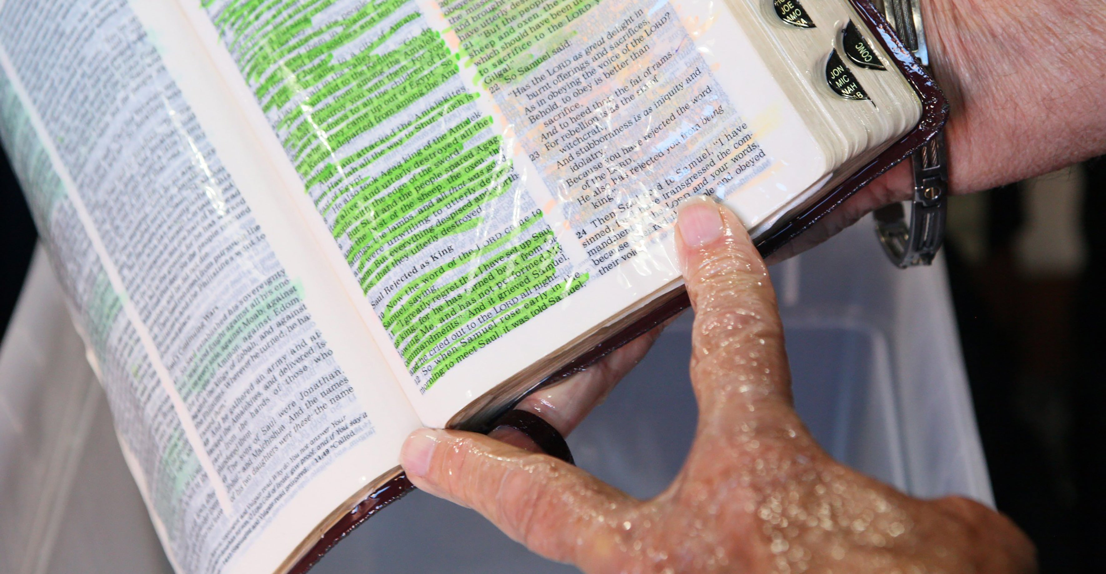 Hands wet with oil open a Bible, whose pages are slicked in oil.