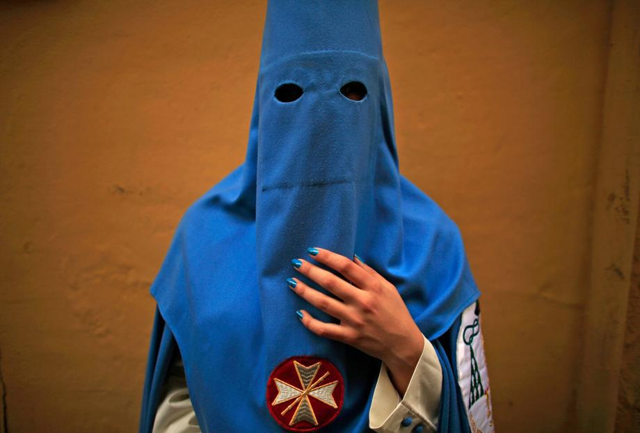"""Macarena, a penitent of """"San Esteban"""" brotherhood, poses for a portrait before making her penance during Holy Week in the Andalusian capital of Seville, southern Spain, March 26, 2013."""