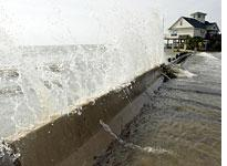 Water crashes over a barrier in Galveston Bay. Click image to expand.