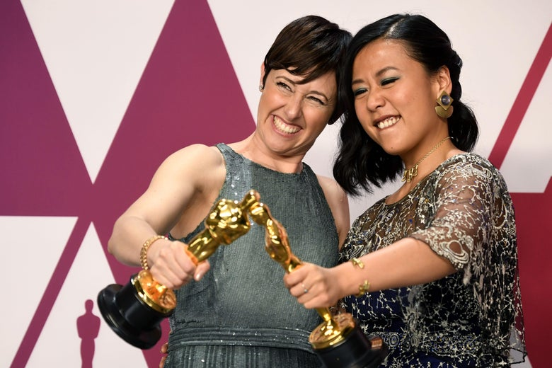 Two women hold Oscar statuettes.