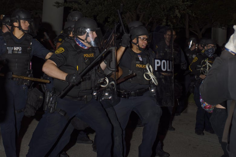 A group of police officers in riot gear with batons raised at night