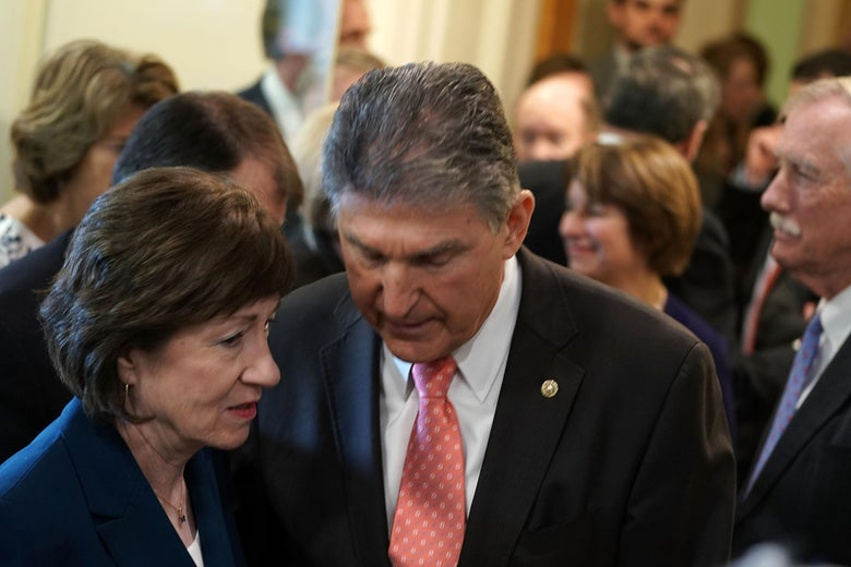 Joe Manchin leans in to speak to Susan Collins in a crowded hallway inside the Capitol on February 15, 2018.
