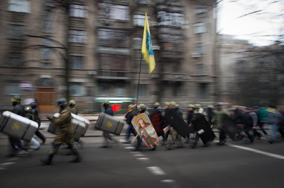 Protesters march in the streets of Kiev carrying flags and decorated shields on Feb. 15, 2014.
