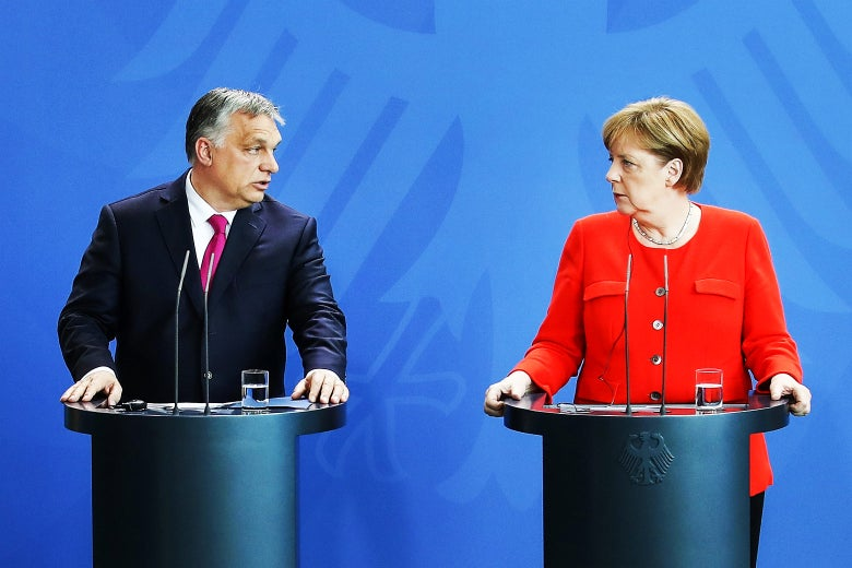 Merkel and Orbán standing at podia during a press conference.