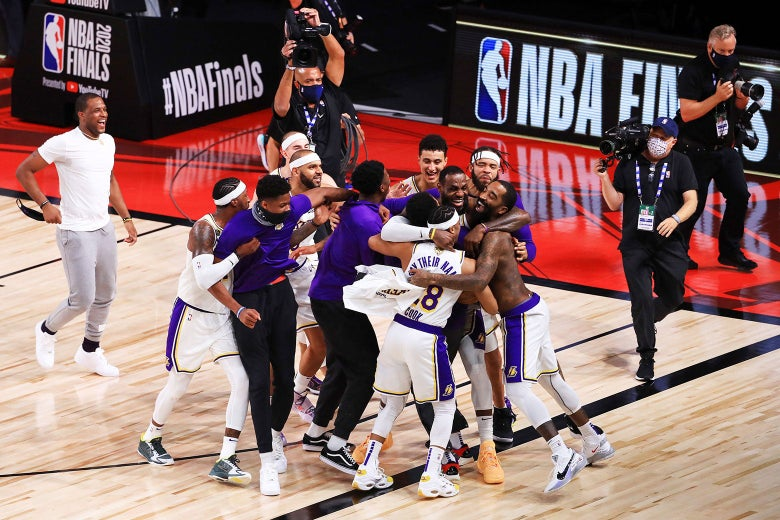 The Lakers hug one another on a gym floor.