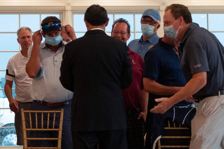 Country club members are handed facemasks to wear as they await the US president's arrival ahead of a news conference in Bedminster, New Jersey, on August 7, 2020.