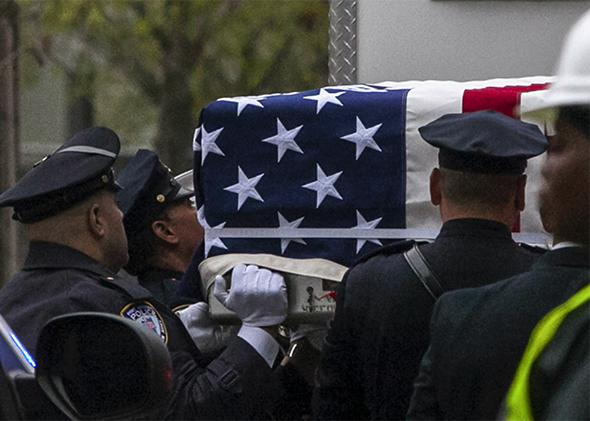 Emergency personnel carry a casket draped with a U.S. flag during the ceremonial transfer of unidentified Sept. 11 remains from the medical examiner's office to a repository at ground zero on May 10, 2014.