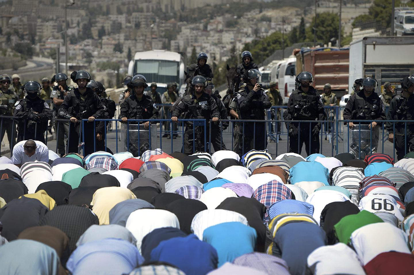 Palestinians perform Friday prayer on the street, outside the Al-Aqsa Mosque after Israeli police.