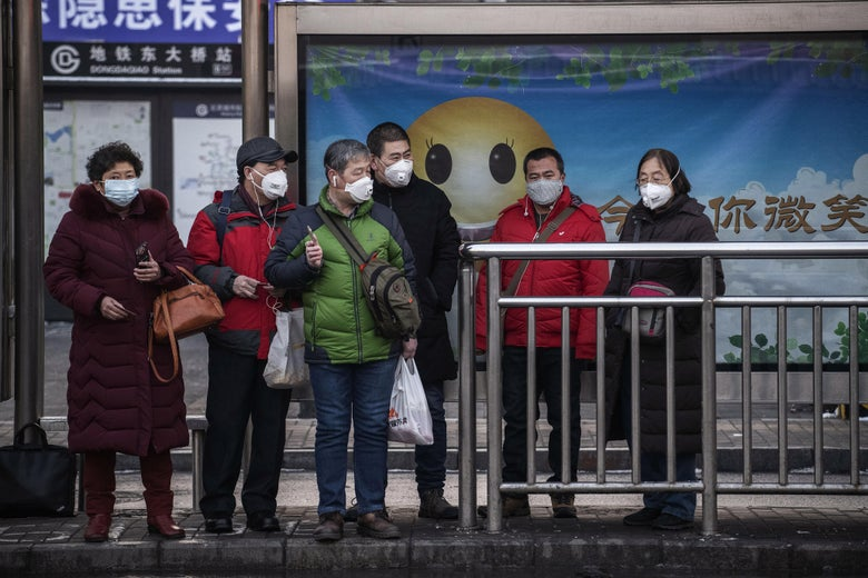 Commuters wearing protective masks wait for a bus on a usually busy street on February 7, 2020 in Beijing, China.
