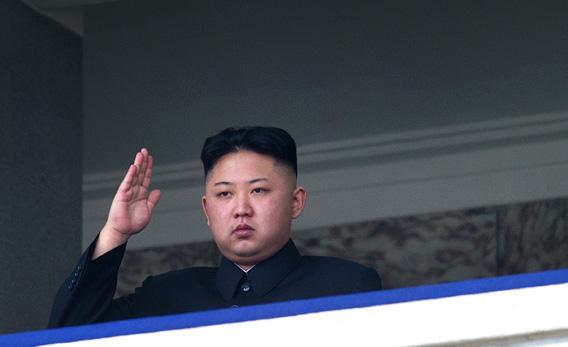 North Korean dear leader Kim Jong-Un salutes as he watches a military parade.