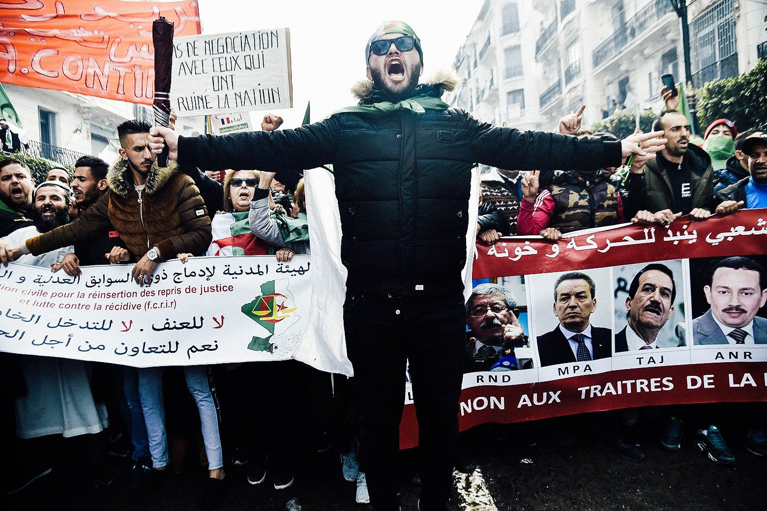 A protester jumps ahead of a marching crowd during a demonstration against ailing President Abdelaziz Bouteflika.