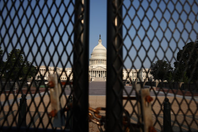 The Capitol is seen behind a fence.