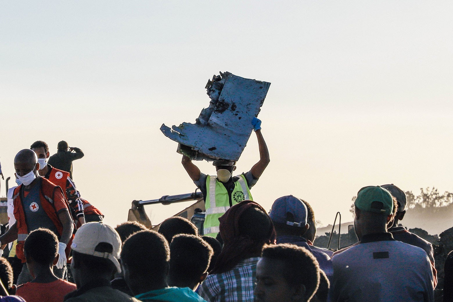 A man carries a piece of debris on his head at the crash site of a Nairobi-bound Ethiopian Airlines flight.