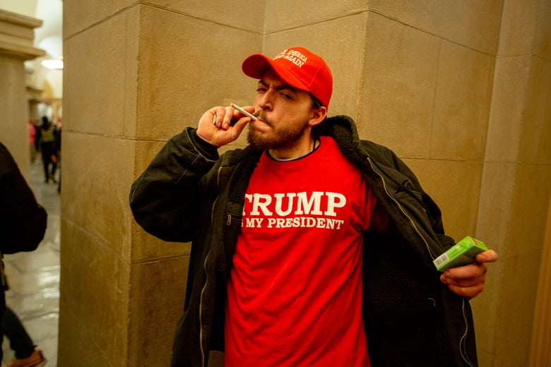 A man smoking a cigarette in a Trump Is My President T-shirt.