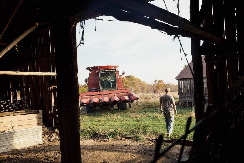 A tractor and a worker viewed from inside a barn in Wisconsin.