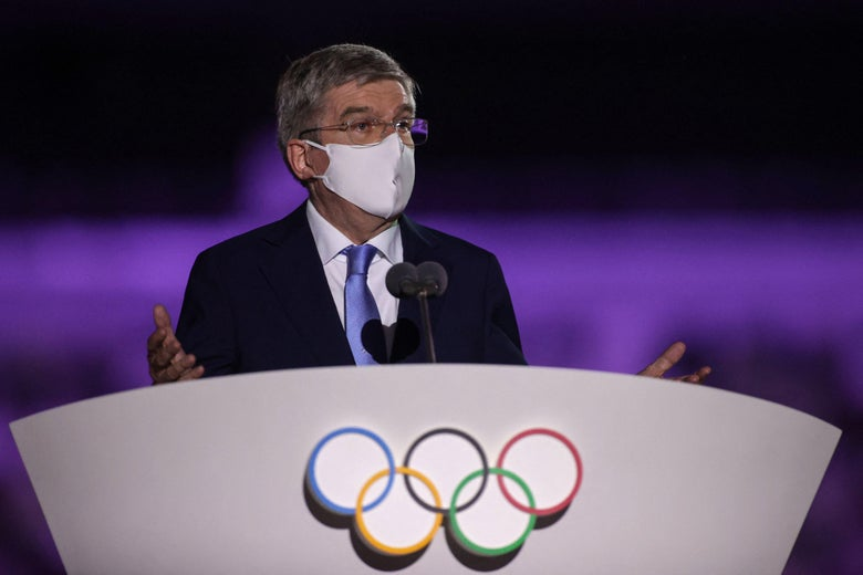 A masked older man in a suit and a mask speaks at a podium with the Olympic rings on it, gesturing with both hands