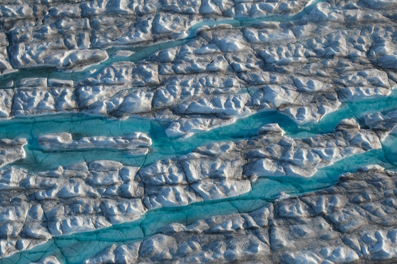 Aerial view of rivers of meltwater carving into the Greenland ice sheet near Ilulissat, Greenland.