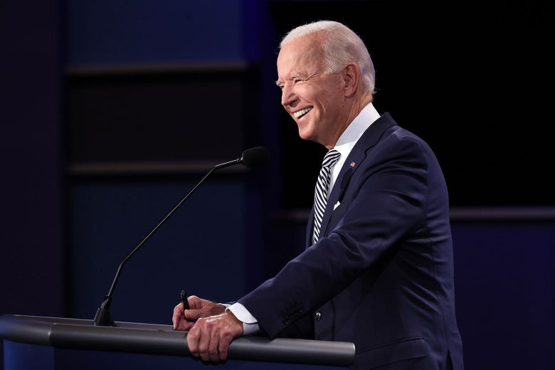 Biden stands on the stage, smiling as he grips his podium