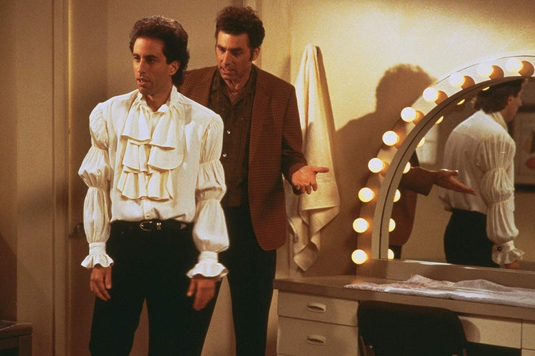 In a dressing room, Jerry Seinfeld wears a white shirt with puffed sleeves and frills on the front with Michael Richards standing behind him.