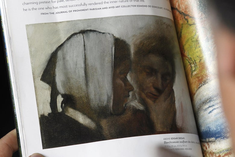 A person reads the 'Sotheby's at auction' magazine with a reproduction of Edgar Degas' painting 'Blanchisseuses souffrant des dents' ('Laundry Women with Toothache') on November 4, 2010 in Paris.