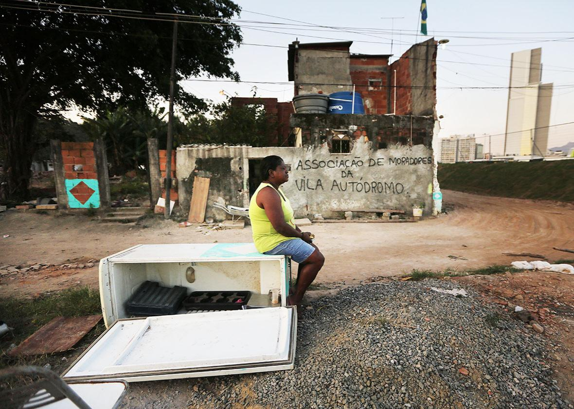 21-year resident Sandra Regina sits in front of her old home while in the process of moving out in the former Vila Autodromo 'favela' community, next to the Olympic Park, in the Barra da Tijuca neighborhood on August 1, 2016 in Rio de Janeiro, Brazil.