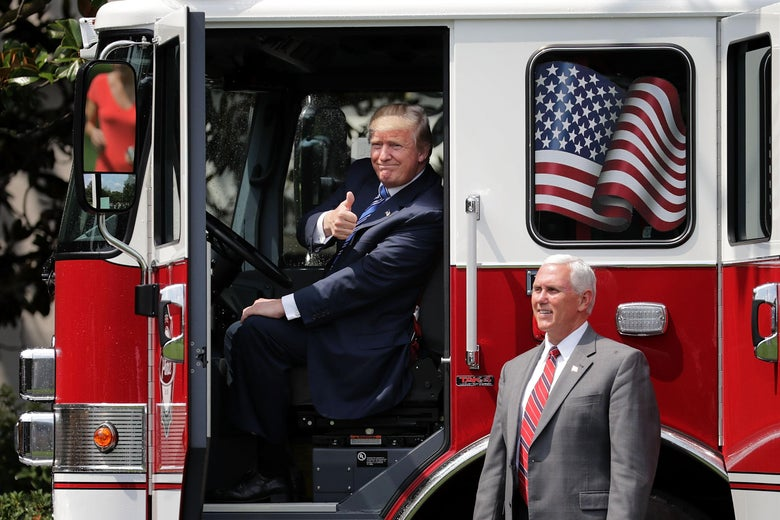 President Donald Trump gives a thumbs-up from inside a fire engine, while Mike Pence stands by.