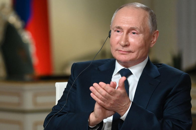 Putin holds his palms together as he wears an earpiece.