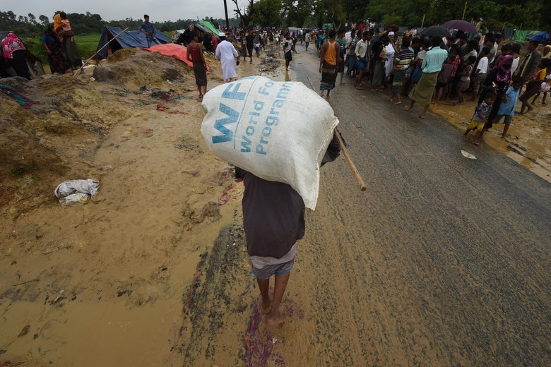 A man carries a World Food Program rice bag on his back as he walks along a dirt road
