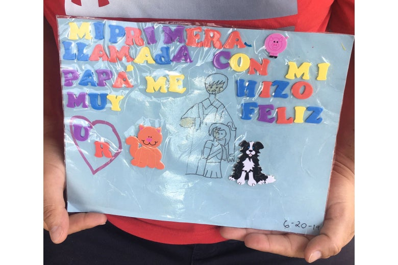 Hands hold up a laminated piece of paper featuring block letters, stickers, and a drawing.
