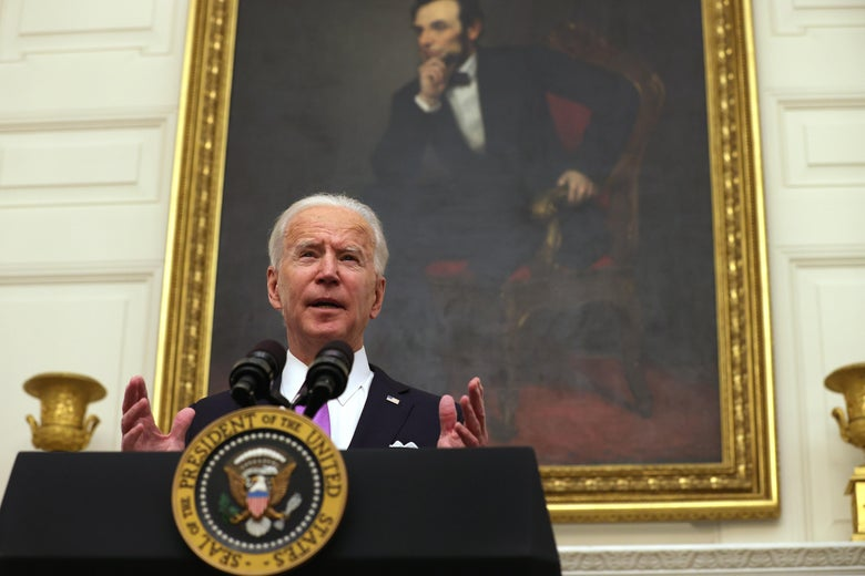 Biden speaks at a podium, standing in front of a portrait of Abraham Lincoln hanging in the State Dining Room