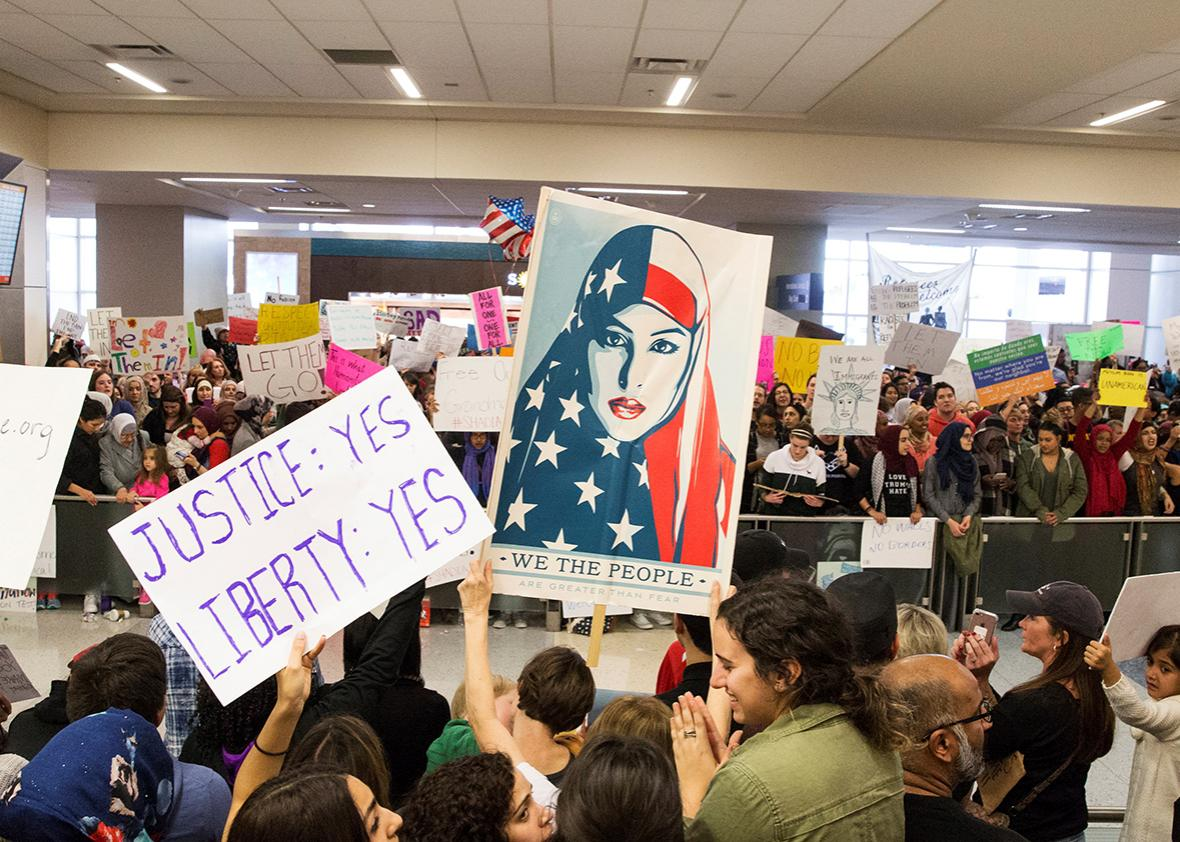 People chant and hold signs as they protest against the travel ban imposed by U.S. President Donald Trump's executive order, at Dallas/Fort Worth International Airport International Arrivals gate in Dallas, Texas, U.S. January 29, 2017.
