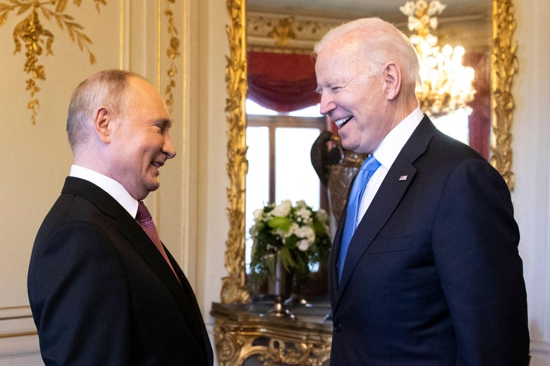 Putin and Biden face each other and smile while talking in an ornate room