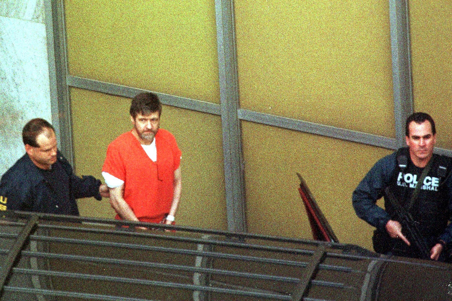 Theodore Kaczynski is led out by U.S. Marshals in Sacramento, California, after admitting to being the Unabomber.