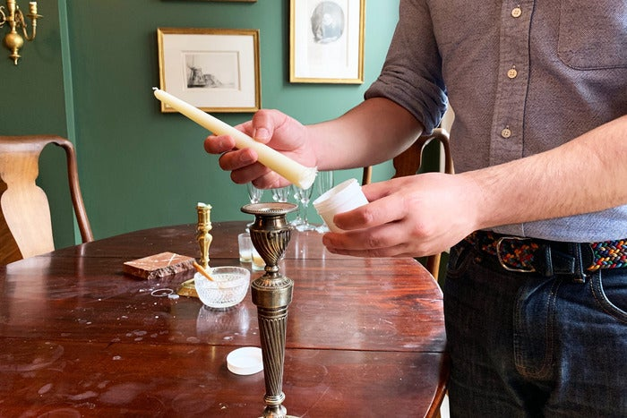 man placing a candle in a candlestick