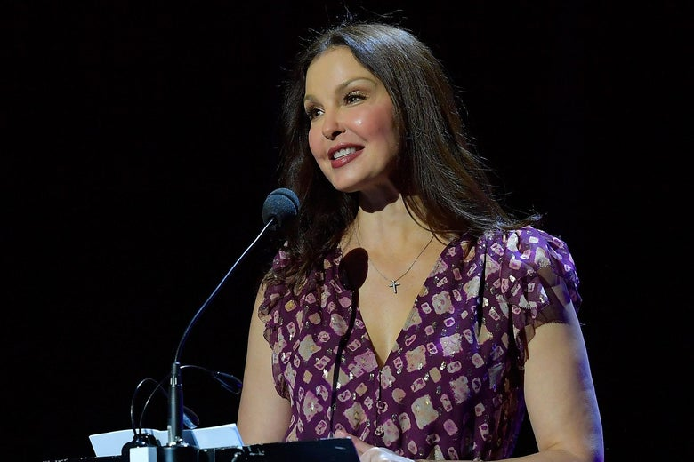 Ashley Judd stands in front of a microphone at a podium.
