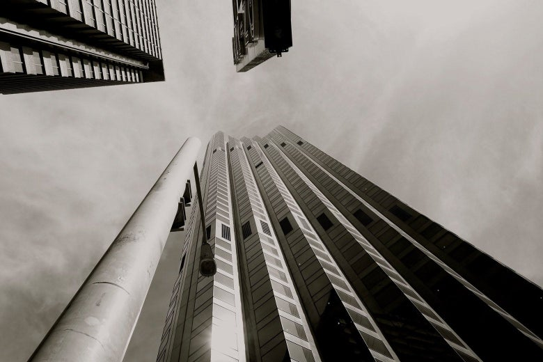 A black-and-white photo, taken from the ground and looking nearly straight up, of a 50-story-ish glass and steel office building.
