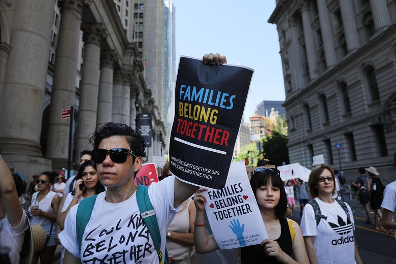 "A man holding a sign that says ""families belong together"" leads a march of protesters with similar signs."