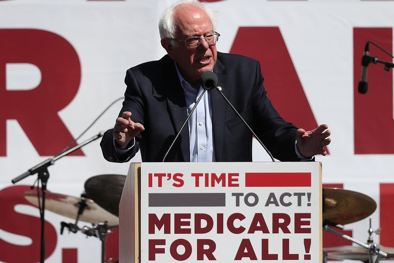"Bernie Sanders speaks from a podium that says ""It's time to act! Medicare for all!"""