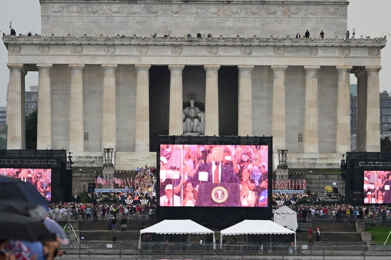 "People gather on the National Mall near a screen showing President Donald Trump delivering a speech during the ""Salute to America"" Fourth of July event at the Lincoln Memorial in Washington, D.C. on July 4, 2019."