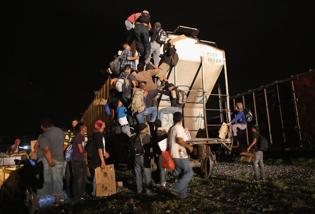 "Arriaga, Mexico Central American migrants climb atop a freight train headed north early on August 4, 2013 in Arriaga, Mexico. Thousands of immigrants ride atop the trains, known as ""la bestia,"" or the beast, during their long and perilous journey through Mexico to the U.S. border. Many of the immigrants are robbed or assaulted by gangs who control the train tops, while others fall asleep and tumble down, losing limbs or perishing under the wheels of the trains. Only a fraction of the immigrants who start the journey will arrive safely on their first attempt to illegally enter the United States."