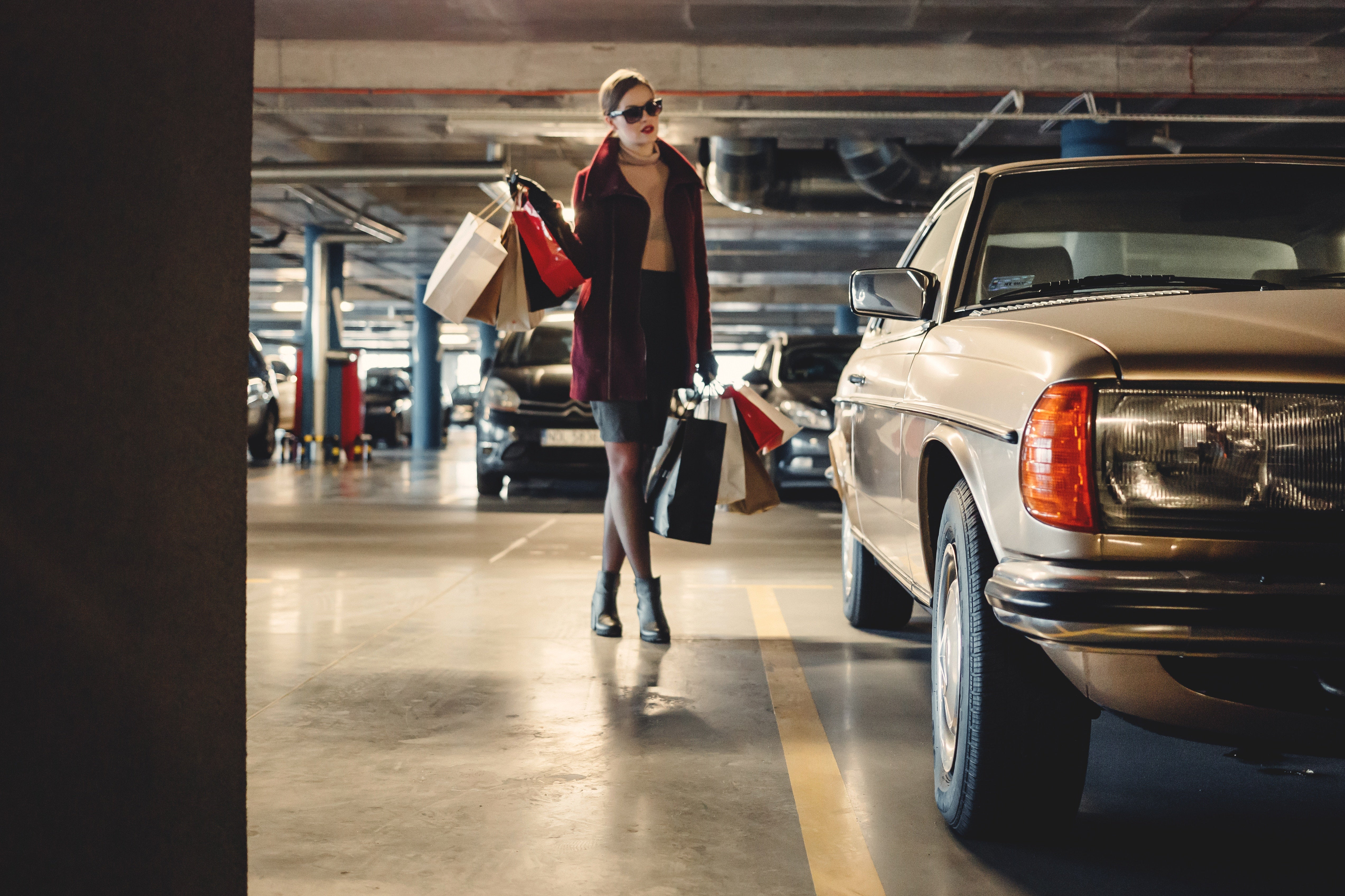 In a parking garage, a fashionable woman carries bags to a car.