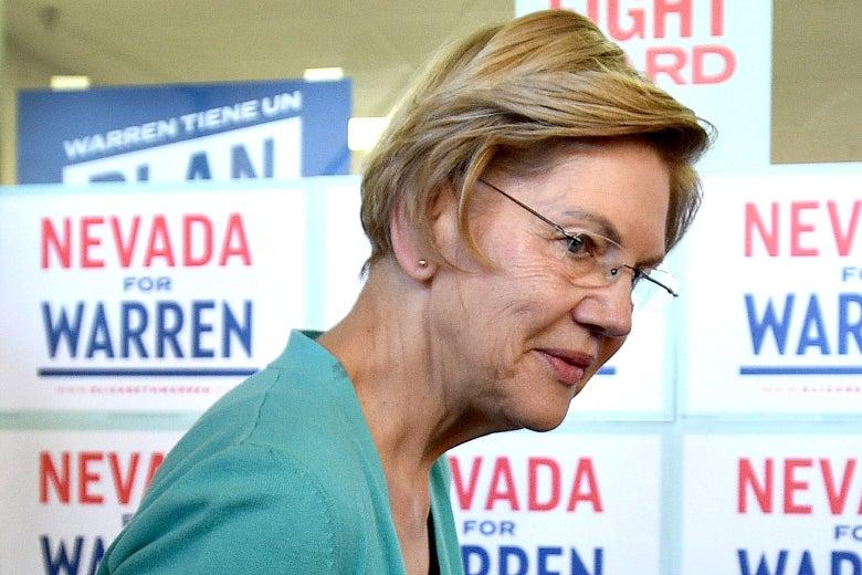 "Elizabeth Warren, viewed in profile, with signs that say ""Nevada for Warren"" behind her."