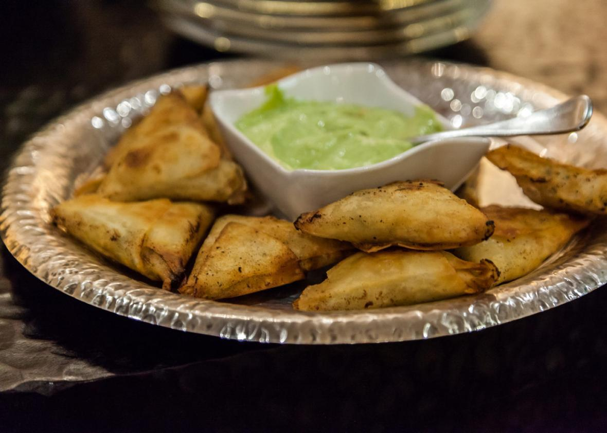 Hojaldries de karne (filo triangles with a meat filling) served with an avocado dip.