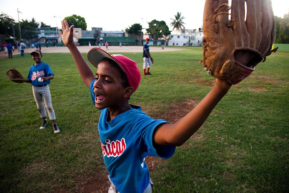 SANTO DOMINGO, DOMINCAN REPUBLIC. A young boy argues ball and strikes with a volunteer umpire during a practice game.
