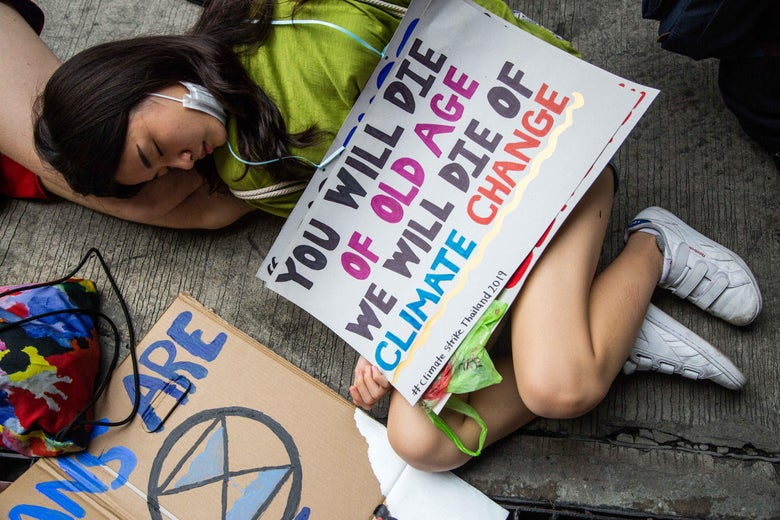 "A girl lies on the ground, under a sign that says ""you will die of old age, we will die of climate change."""