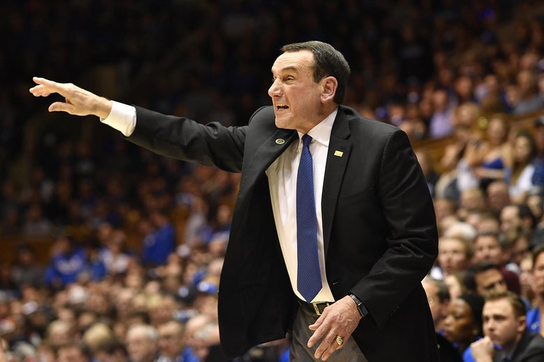 Coach K gesticulating and yelling in a suit on the sideline, as he does
