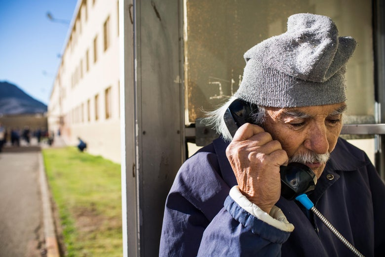 An elderly man talks on a wired phone next to a prison yard.