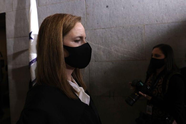 Amy Coney Barrett stands in a dark hallway wearing a black mask